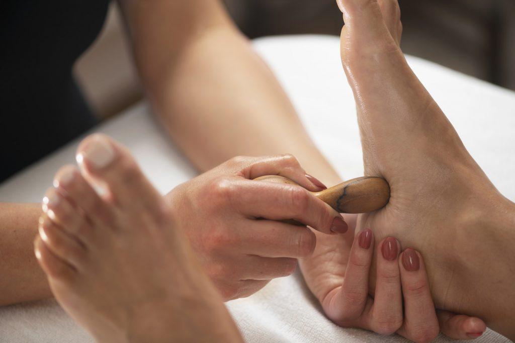 Foot Massage with Wooden Massage Stick. Reflexologist Applying Pressure to Clients Foot